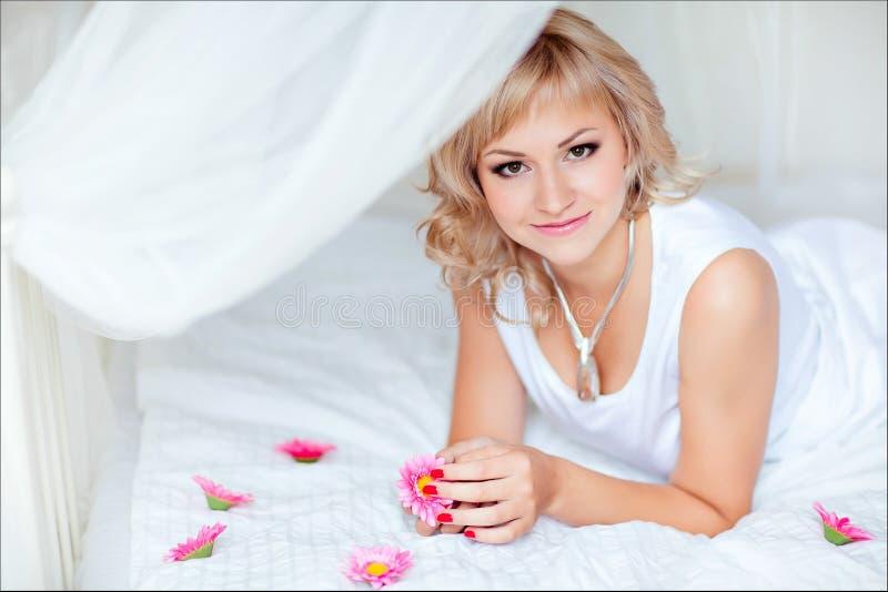 Gullig blond flicka som ligger på en vit säng som omges av liten flowe royaltyfria bilder