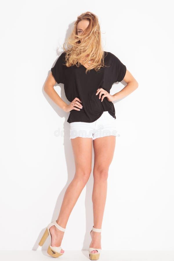 Gullig blond flicka som poserar, medan hår täcker hennes framsida arkivfoto