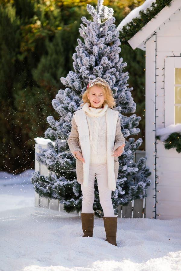 Gullig blond flicka under den fallande snön nära det lilla huset och detäckte träden Nytt år och jul Time arkivfoto