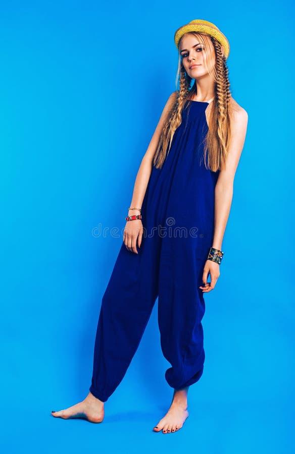 Gullig blond kvinna i blå overall och gulinghatt fotografering för bildbyråer