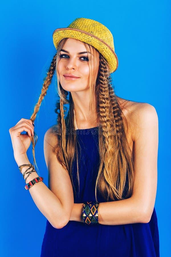Gullig blond kvinna i overall- och sugrörhatt fotografering för bildbyråer
