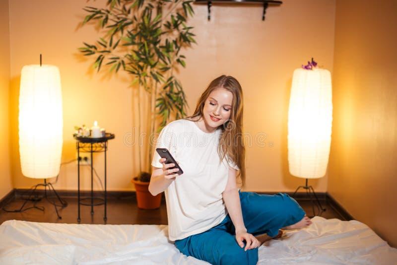 Gullig blond kvinna som använder en smartphone, medan vänta massage på brunnsorten arkivfoto