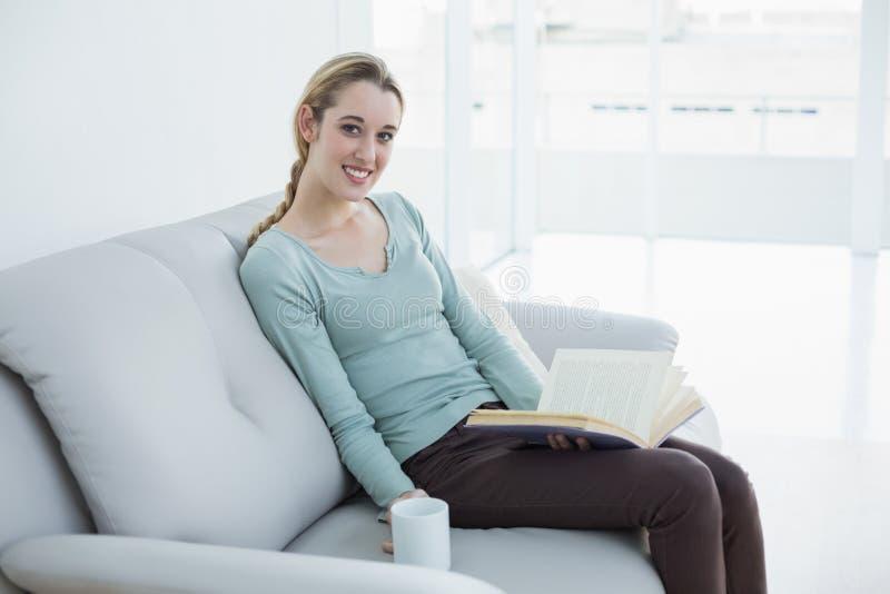 Gullig blond kvinna som rymmer en bok och en kopp, medan sitta på soffan arkivbild