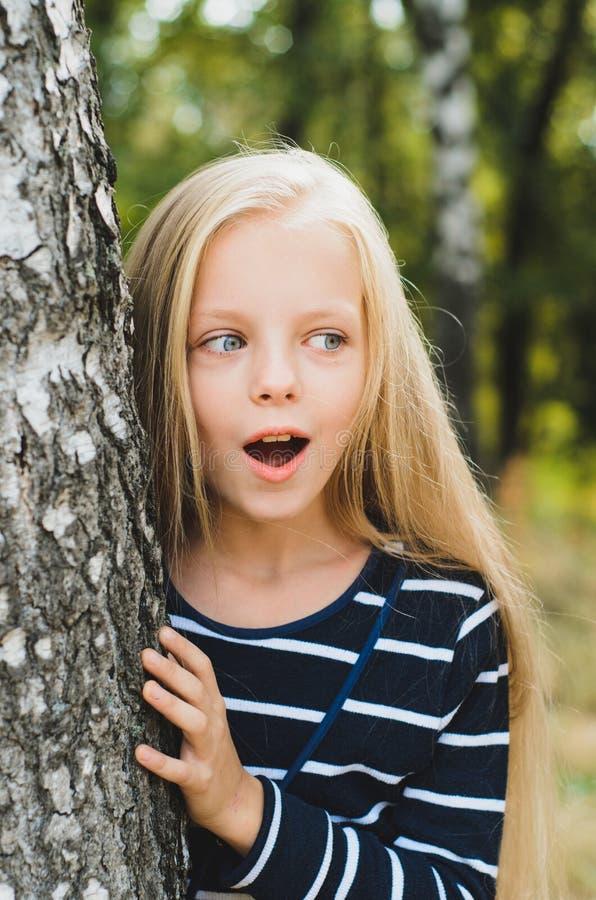 Gullig blond liten flickastående nära trädbjörk royaltyfria foton