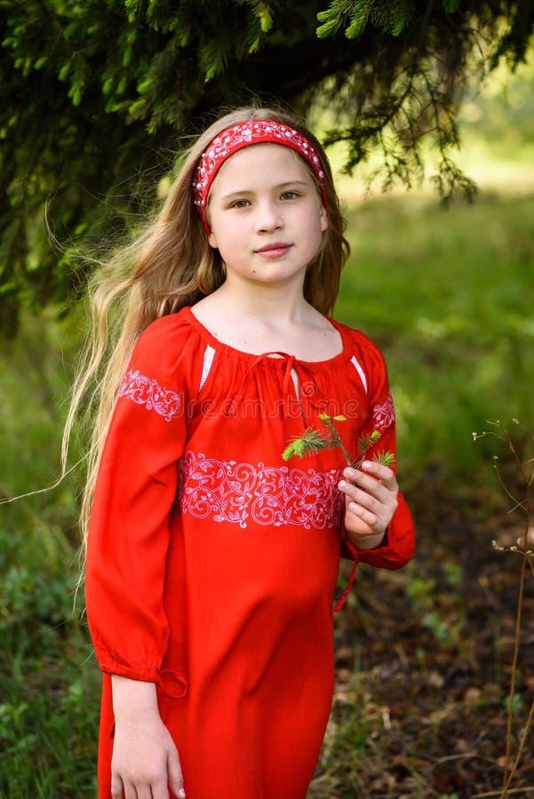 Gullig blond ung flicka som poserar i en traditionell röd klänning för ryss nära granträd arkivbilder