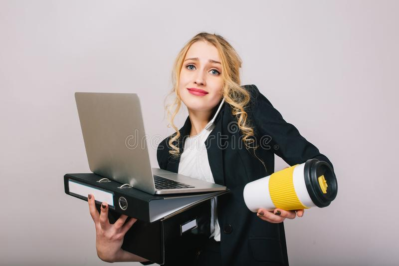 Gullig blond ung kontorskvinna i den vita skjortan, svart omslag, med bärbara datorn, mapp, kaffe som går isolerat på vit royaltyfria foton