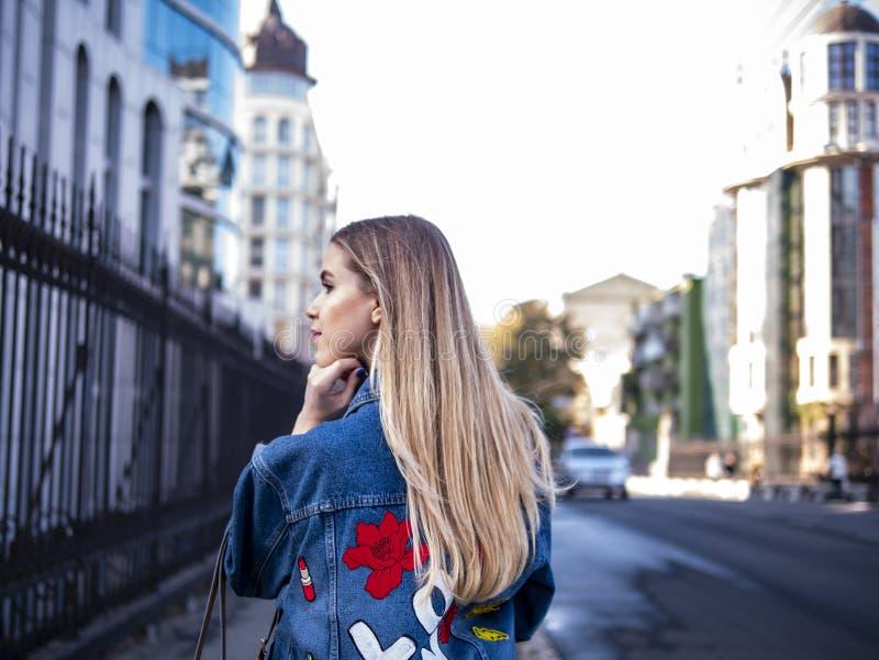 Gullig blondin som är tonårig med flödande hår i ett grov bomullstvillomslag på den utomhus- bron royaltyfri bild