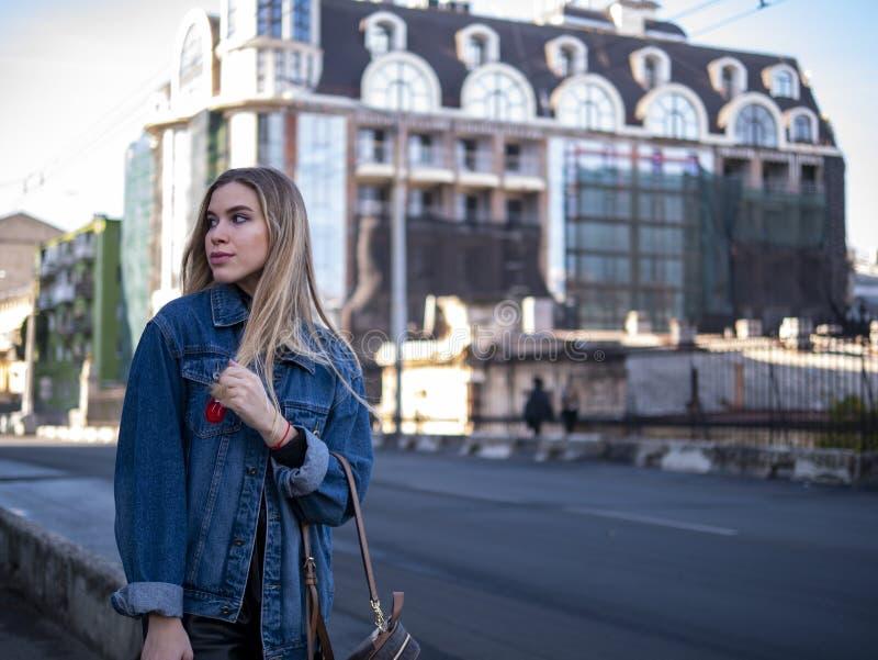 Gullig blondin som är tonårig med flödande hår i ett grov bomullstvillomslag på den utomhus- bron royaltyfri foto