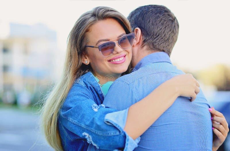 Gullig blondin som kramar hennes pojkvän Dela ett älska ögonblick royaltyfri bild