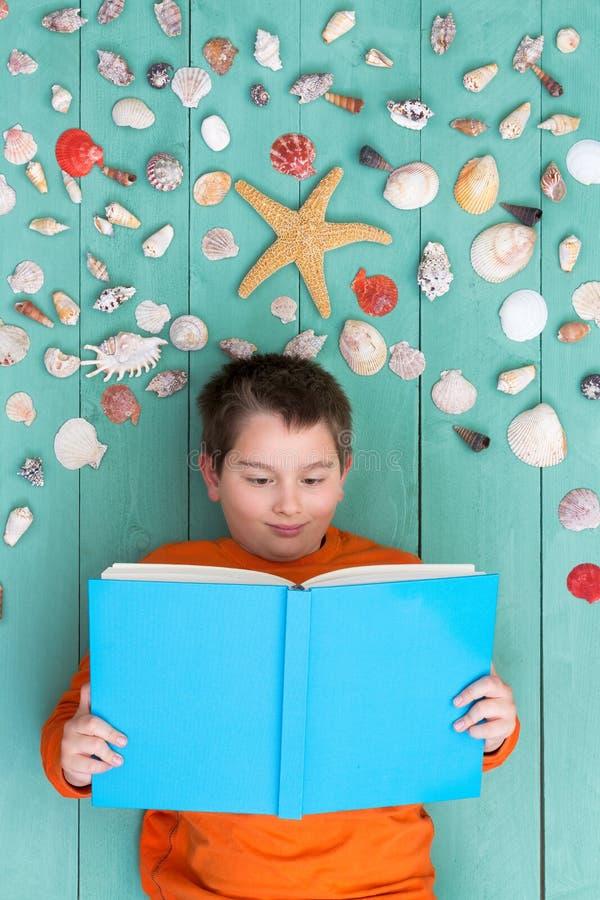Gullig bok för pojkeläsningmellanrum nära snäckskal royaltyfri foto