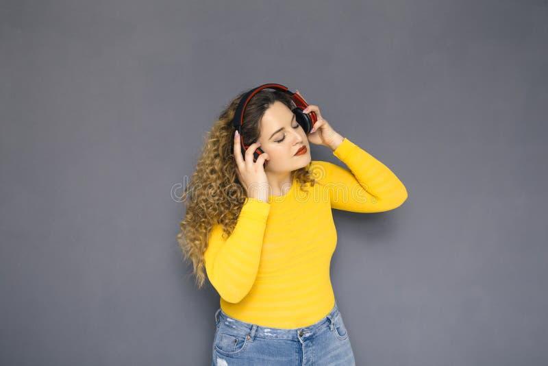 Gullig brunett plus formatkvinna med lockigt hår i gul tröja arkivbild