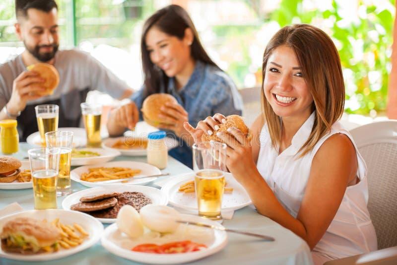 Gullig brunett som äter en hamburgare med hennes vänner arkivfoton
