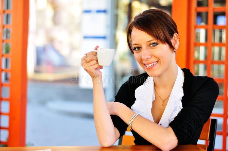 Gullig brunett som rymmer en kopp i en hand royaltyfri foto