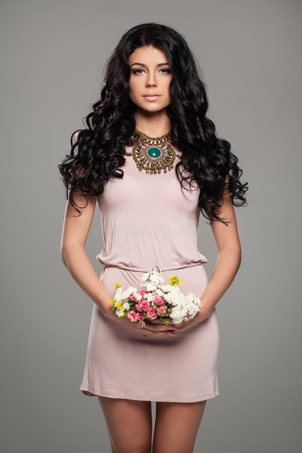 Gullig brunettkvinna i sommarrosa färgklänning fotografering för bildbyråer