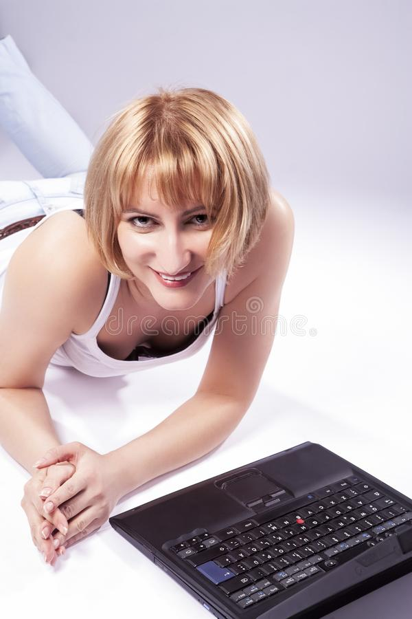 Gullig Caucasian blond kvinna med bärbara datorn på att le för golv arkivfoto