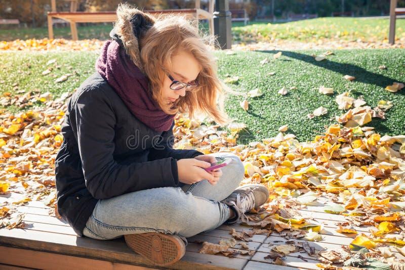 Gullig Caucasian blond tonårs- flicka med mobiltelefonen fotografering för bildbyråer