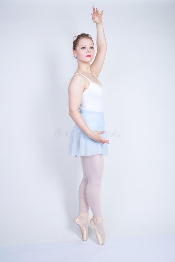 Gullig caucasian flicka i balettkläder som lär att vara en ballerina på en vit bakgrund i studion plus drömmar för ung kvinna för fotografering för bildbyråer
