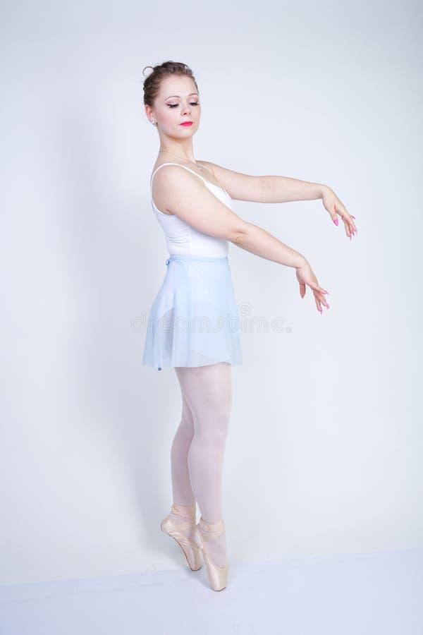 Gullig caucasian flicka i balettkläder som lär att vara en ballerina på en vit bakgrund i studion plus drömmar för ung kvinna för arkivbild