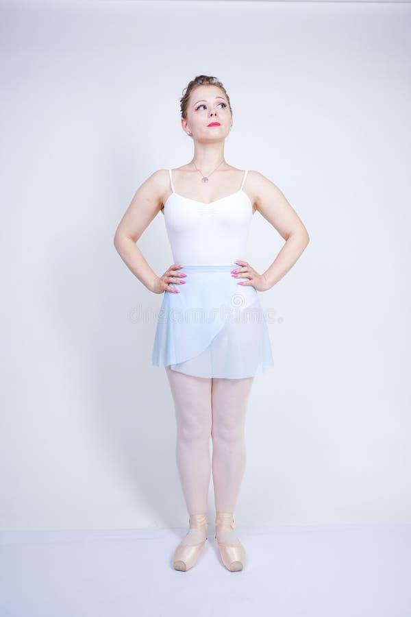 Gullig caucasian flicka i balettkläder som lär att vara en ballerina på en vit bakgrund i studion plus drömmar för ung kvinna för arkivfoton