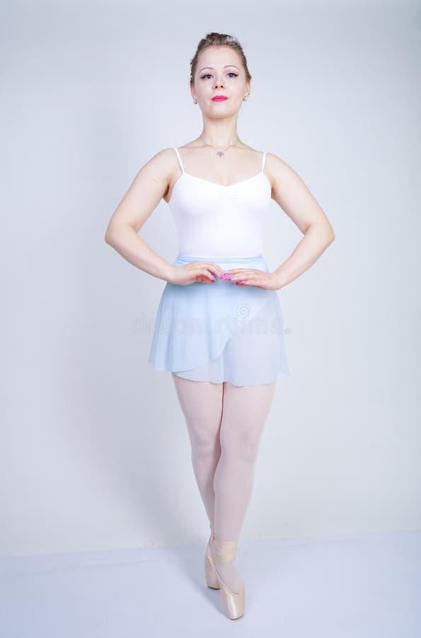 Gullig caucasian flicka i balettkläder som lär att vara en ballerina på en vit bakgrund i studion plus drömmar för ung kvinna för royaltyfri bild