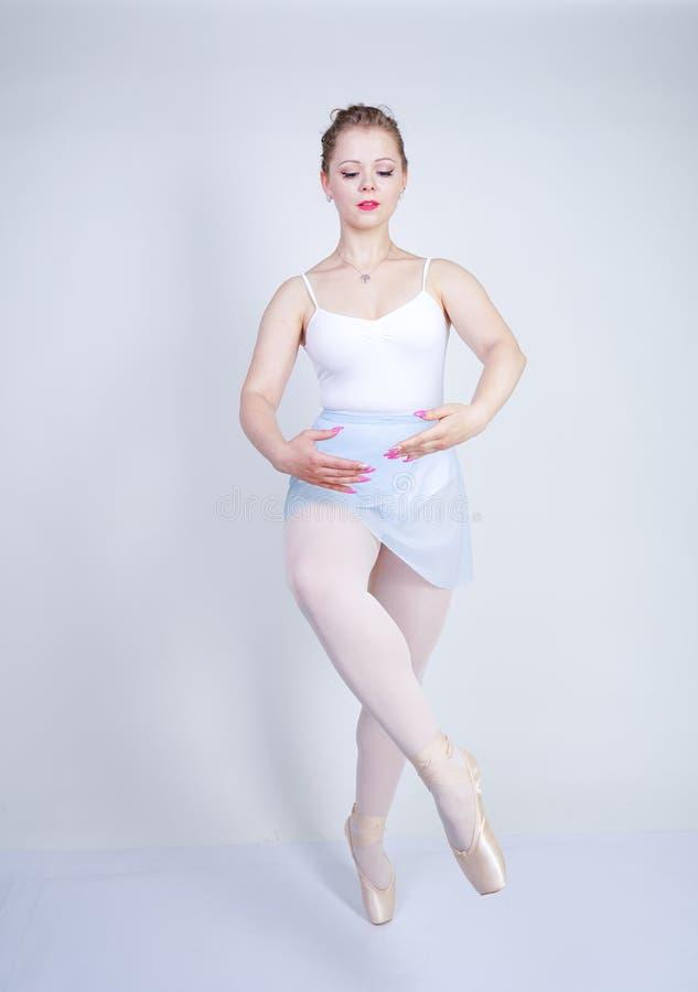 Gullig caucasian flicka i balettkläder som lär att vara en ballerina på en vit bakgrund i studion plus drömmar för ung kvinna för arkivfoto