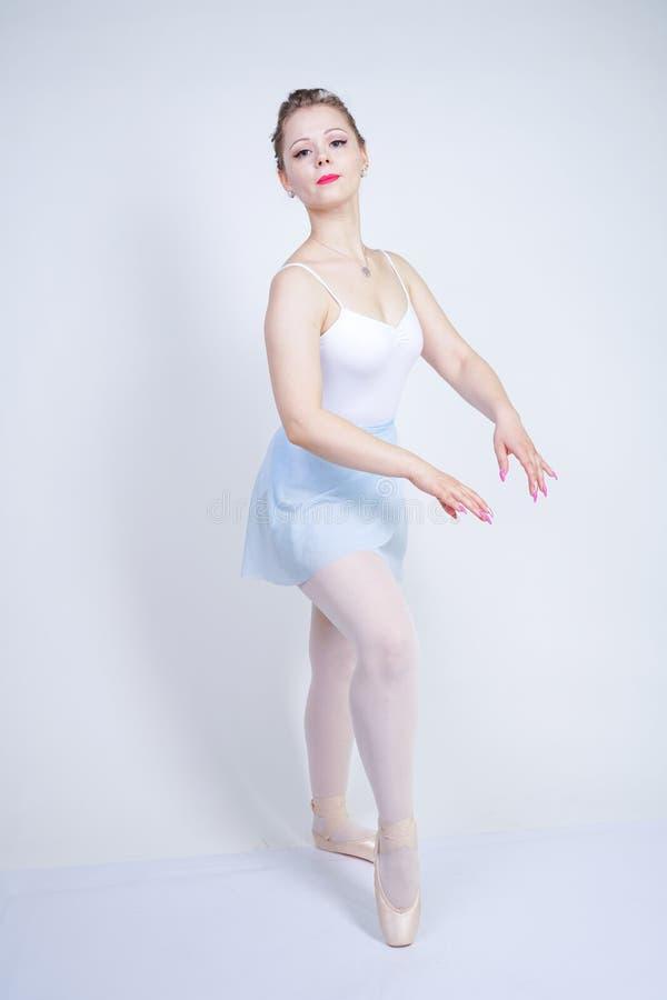 Gullig caucasian flicka i balettkläder som lär att vara en ballerina på en vit bakgrund i studion plus drömmar för ung kvinna för royaltyfri fotografi