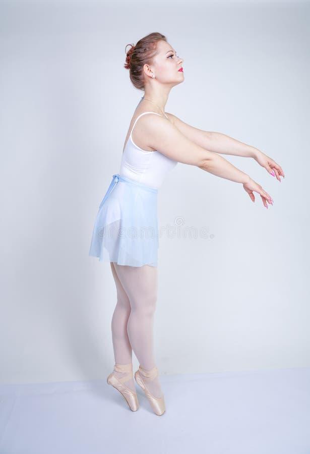 Gullig caucasian flicka i balettkläder som lär att vara en ballerina på en vit bakgrund i studion plus drömmar för ung kvinna för royaltyfria foton