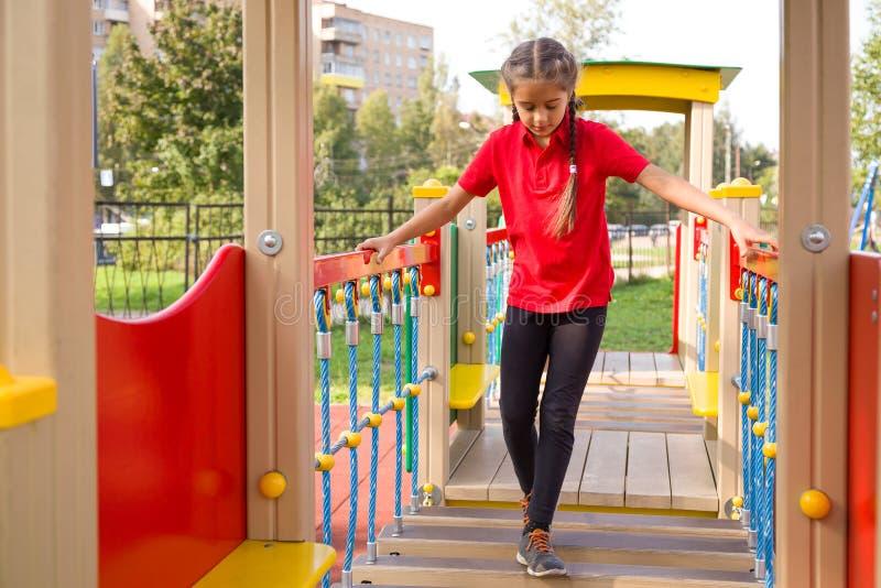 Gullig caucasian flicka som spelar på lekplats och att gå på att svänga moment och att försöka till keeep hennes jämvikt fotografering för bildbyråer