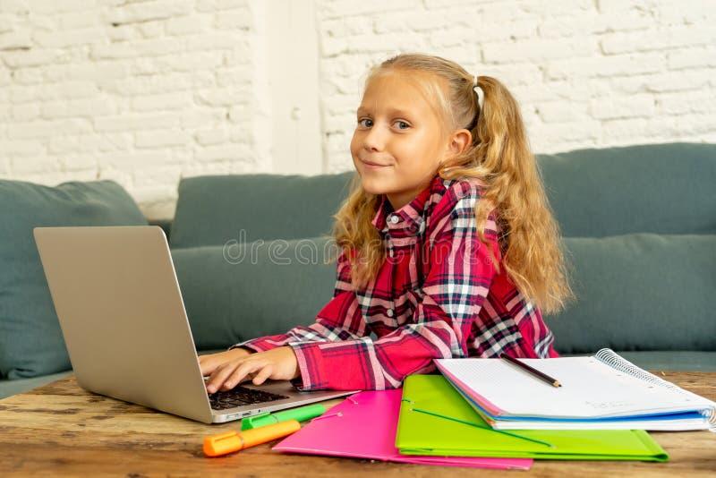 Gullig caucasian gladlynt elementär student som känner sig lycklig, medan göra läxa och studera på hennes bärbar dator i vardagsr arkivfoto