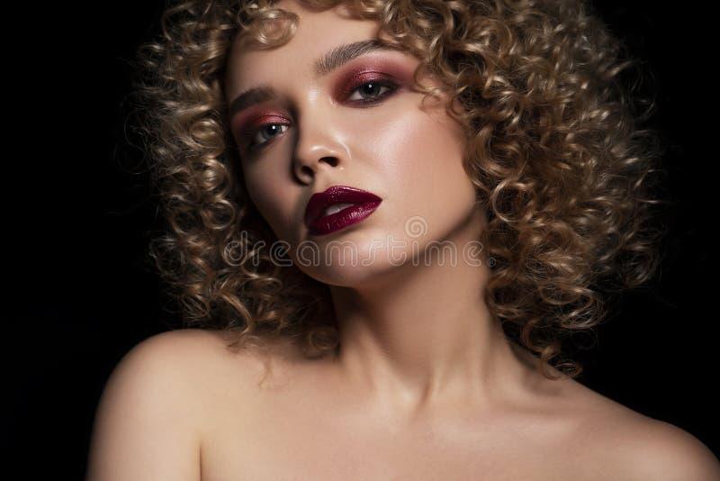 Gullig caucasian kvinna med den afro krullningsfrisyren på en mörk bakgrund Hon bär mörk afton, eller podiet utgör med röd mascar royaltyfri foto