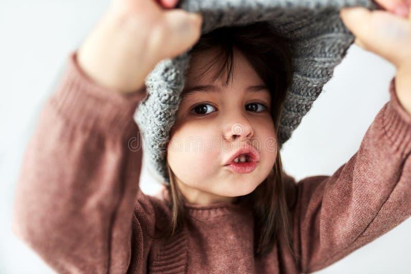 Gullig Caucasian liten flicka som spelar tittutet med den varma gråa hatten för vinter, bärande tröja som isoleras på en vit stud royaltyfria bilder