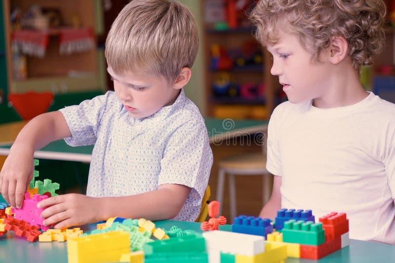 Gullig caucasian pojke i en vit skjorta som spelar med färgrika konstruktördetaljer Aktiviteter med barn i dagis arkivfoto