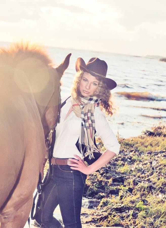 Gullig cowgirl med henne häst på golfen. fotografering för bildbyråer