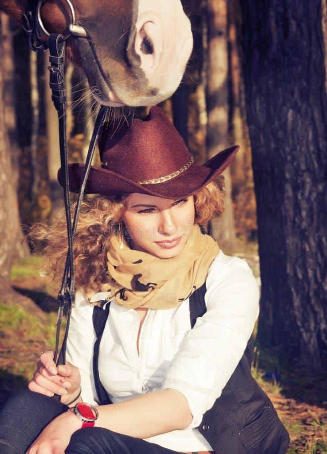 Gullig cowgirl med henne röd häst. royaltyfri fotografi