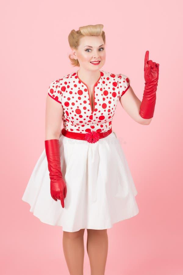 Gullig dam i röda handskar som upp pekar hennes finger och att le royaltyfria bilder