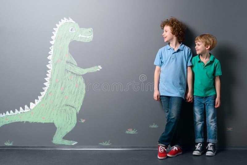 Gullig dinosaurie och två pojkar royaltyfri fotografi