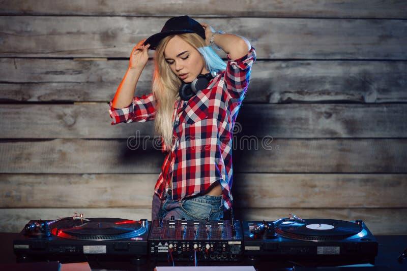 Gullig dj-kvinna som har gyckel som spelar musik på klubbapartiet royaltyfri foto