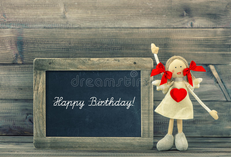Gullig docka med röd hjärta Älskvärd födelsedaggarnering Semestrar c arkivfoto