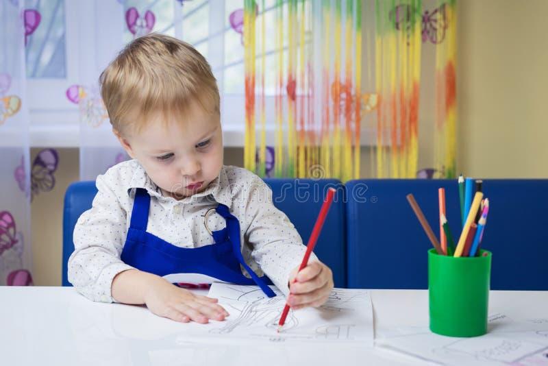 Gullig eftertänksam caucasian pojke 3 år gammal teckning med den kulöra blyertspennan i en anteckningsbok som sitter på ett skriv royaltyfria bilder