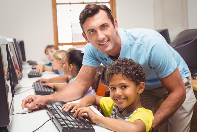 Gullig elev i datorgrupp med läraren som ler på kameran fotografering för bildbyråer