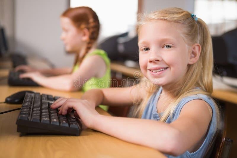 Gullig elev i datorgrupp som ler på kameran royaltyfria foton
