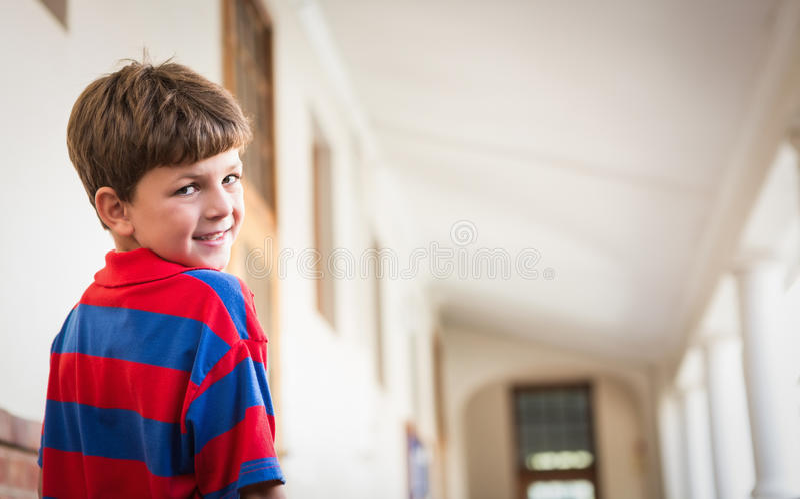 Gullig elev som ler på kameran i korridor royaltyfri fotografi