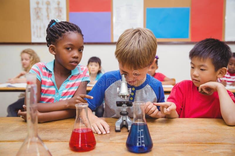 Gullig elev som ser till och med mikroskopet royaltyfria bilder