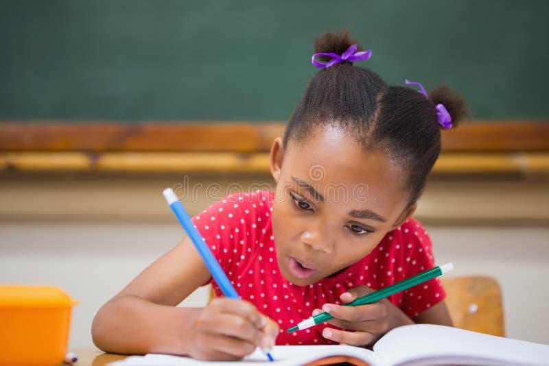 Gullig elevhandstil på skrivbordet i klassrum royaltyfria foton