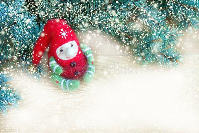 Gullig färgrik julleksakälva bredvid nya naturliga filialer av julgranen på en träbakgrund arkivfoton