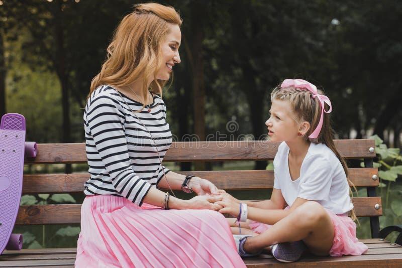 Gullig förskole- dotter som har konversation med hennes moder royaltyfri foto
