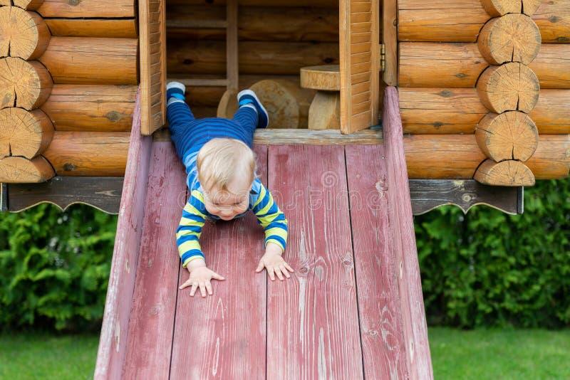 Gullig förtjusande caucasian litet barnpojke som har gyckel som ner glider träglidbanan på eco-vänskapsmatch den naturliga lekpla arkivbilder