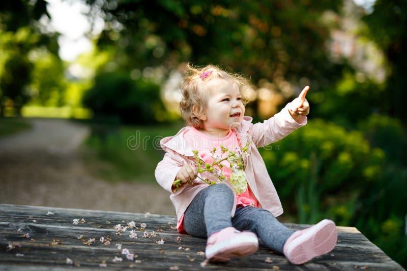 Gullig förtjusande litet barnflicka som spelar med blommande kastanjebruna blommor Behandla som ett barn lite barnet som går för  arkivfoton