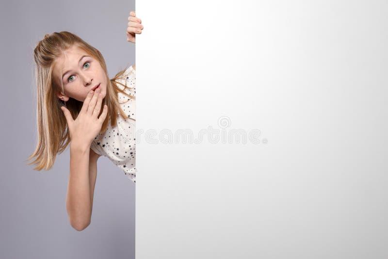 Gullig förvånad flicka med det tomma advertizingbrädet royaltyfri foto