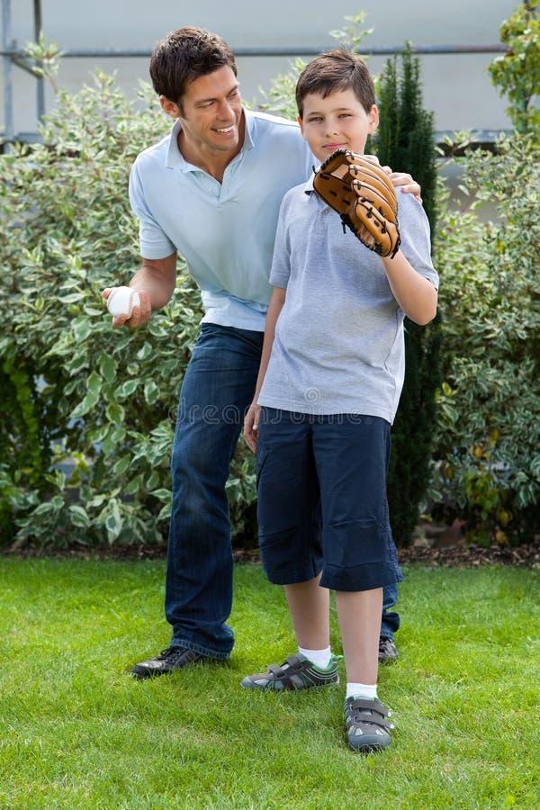 gullig fader för baseballpojke hans little som leker arkivbilder